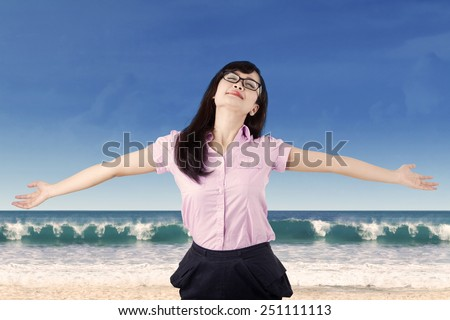 Carefree woman is stress free and holds her arms out for freedom and peace of mind. - stock photo