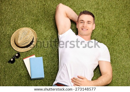 Carefree young man lying on grass and looking at the camera with a pair of sunglasses, a hat and a couple of books beside him  - stock photo