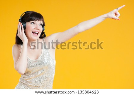 Carefree young woman listening to music and gesturing, yellow background - stock photo