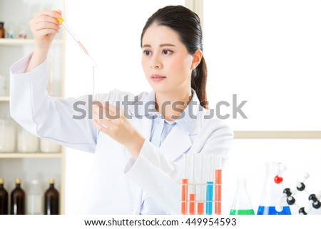 Careful, meticulous work of asian female scientist use dropper in Laboratory - stock photo