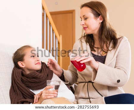 Careful mother giving medicinal sirup to sick daughter at home - stock photo