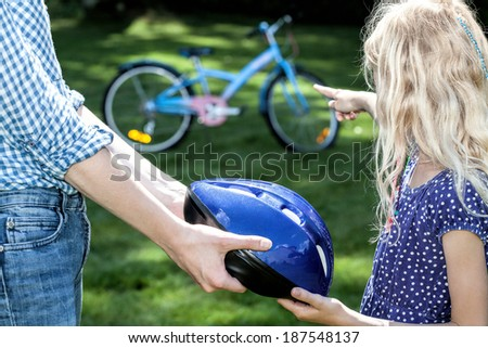 Careful parent protecting his child from a bike accident - stock photo