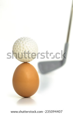 CAREFUL STRIKE A golf-ball on top of an egg, challenging for hitting the ball without breaking the egg. - stock photo