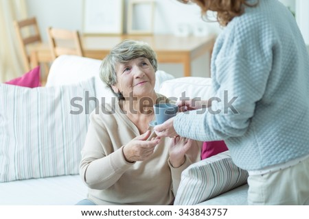 Caregiver giving elder woman cup of coffee - stock photo