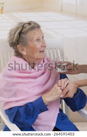 Caregiver giving glass of water to an elegant senior woman at nursing home - stock photo