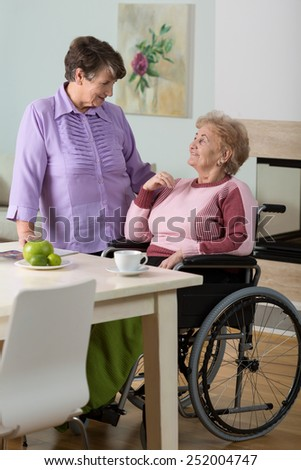 Caregiver helping disabled senior woman using wheelchair - stock photo