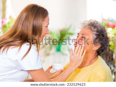 Caregiver rubs the face cream on the elderly womans face - stock photo