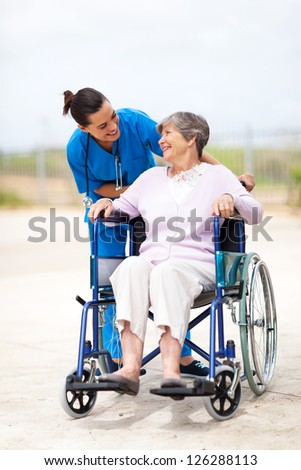 caregiver talking to disabled senior woman outdoors - stock photo
