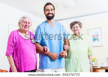 Caregiver with senior women in nursing home - stock photo