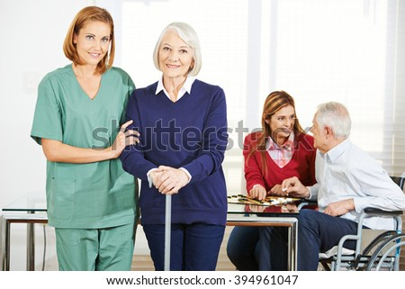 Caregiver working with happy senior people in nursing home - stock photo