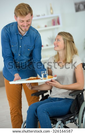 Carer giving lunch to you woman - stock photo