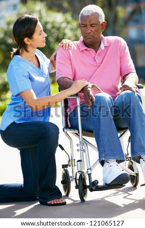 Carer Pushing Unhappy Senior Man In Wheelchair - stock photo