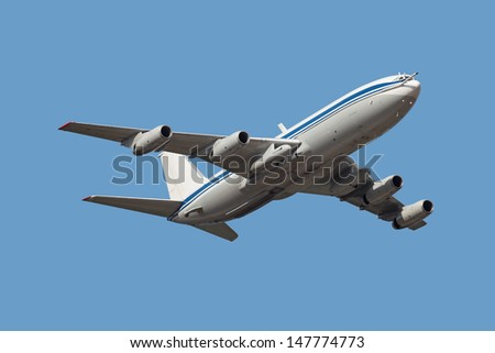 Cargo aircraft in flight, is isolated on a blue background - stock photo