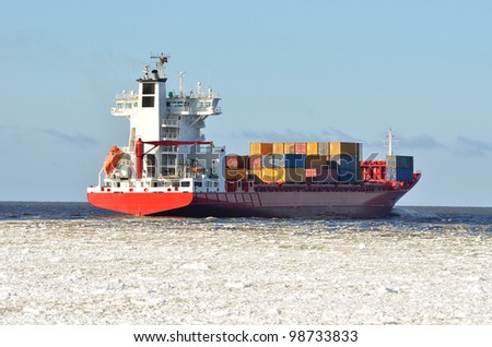 cargo container ship sailing in sea full of ice in winter - stock photo