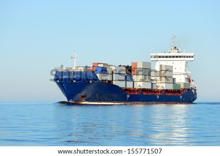 cargo container ship sailing in still water - stock photo
