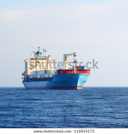 cargo conteiner ship sailing in still water - stock photo