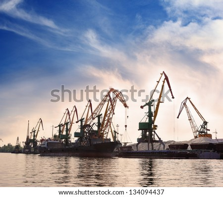 Cargo cranes in the dock by the water over blue sky - stock photo