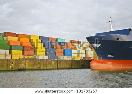 cargo freight containers stacked at harbor terminal with big container-ship - stock photo