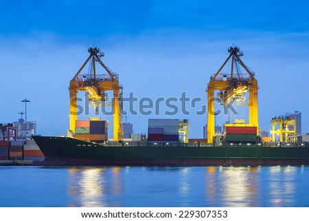 Cargo ship and crane at port reflect on river, twilight time. - stock photo