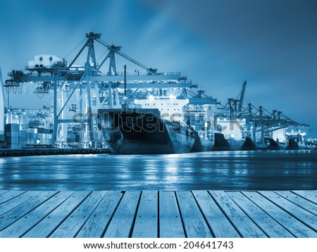 Cargo ship and crane at port reflect with river, twilight time (blue color tone). - stock photo