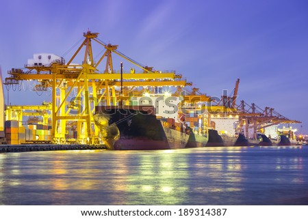 Cargo ship and crane at port reflect with water, twilight time. - stock photo