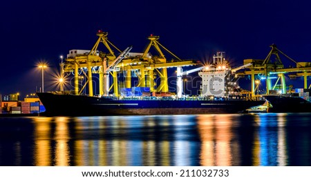 Cargo ship and crane at port, twilight time. - stock photo