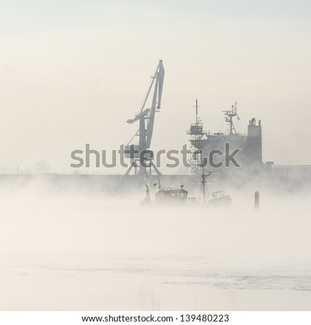 Cargo ship and cranes silhouettes in fog - stock photo