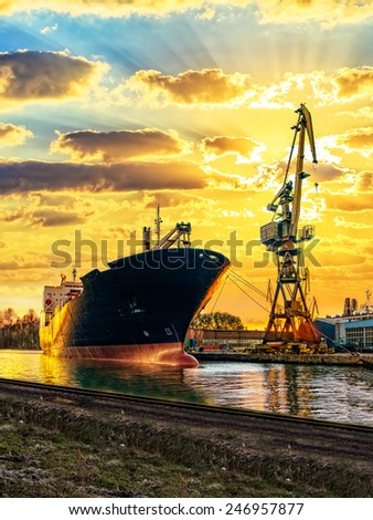 Cargo ship and the port at sunset. - stock photo