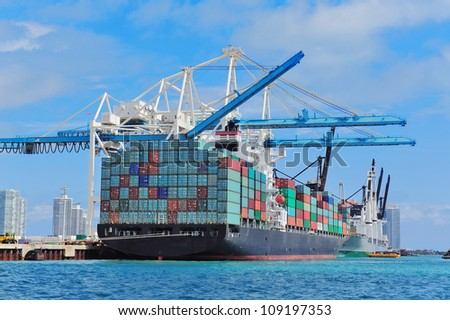 Cargo ship at Miami harbor with crane and blue sky over sea. - stock photo