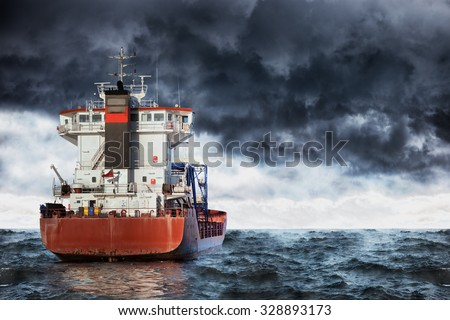 Cargo ship at sea during a storm. - stock photo