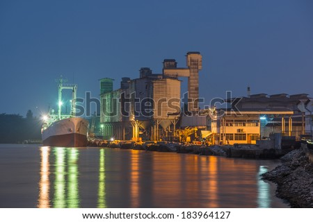 Cargo ship at the industrial building - stock photo