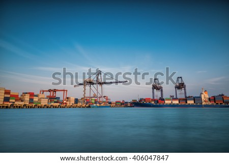 Cargo ship at Trade Port harbor with crane and blue sky over sea at sunrise - stock photo