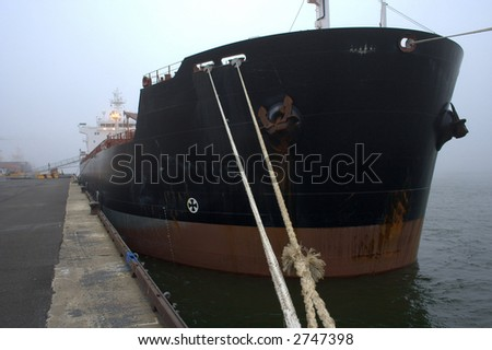 Cargo ship being unloaded - stock photo