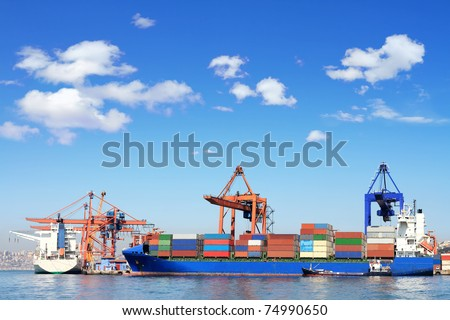 Cargo ship, containers and cranes in sea port - stock photo