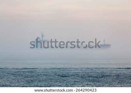 Cargo ship in fog - stock photo