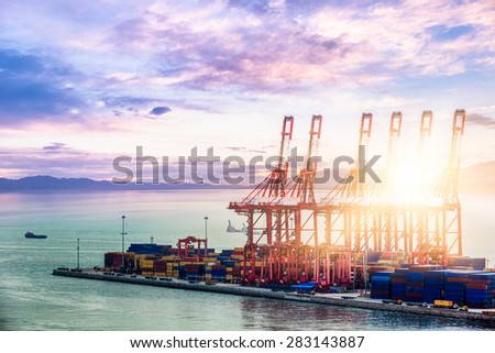 Cargo ship in the harbor at sunset. - stock photo