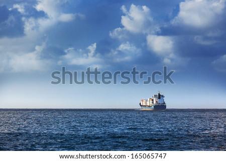 cargo ship in the ocean in the sky - stock photo