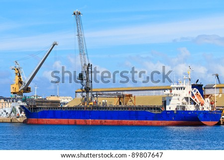 Cargo ship is being unloaded in port - stock photo