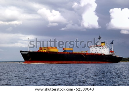 cargo ship is leaving port sailing away - stock photo