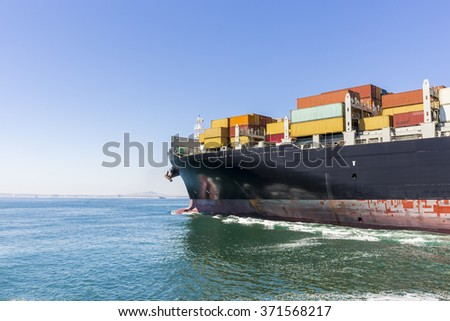 Cargo ship loaded with containers sailing away. - stock photo