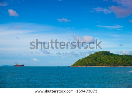 Cargo ship near the island. Moored offshore to wait for a logistics. - stock photo