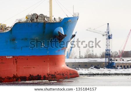 cargo ship's bow heading forward against port cranes - stock photo
