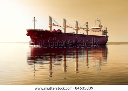 cargo ship sailing in still water against sunset sky - stock photo