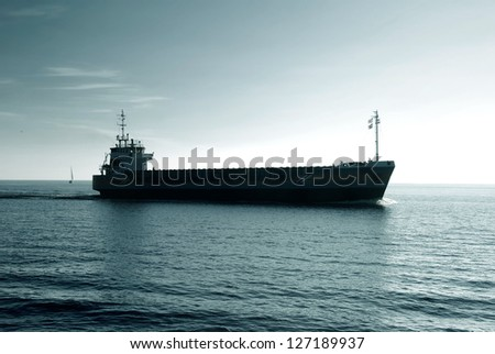 cargo ship sailing in still water heading for the port - stock photo
