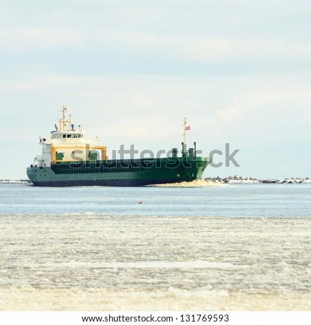 Cargo ship sailing to the port - stock photo
