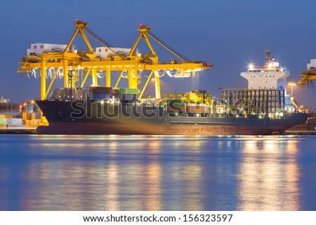 Cargo ship unloading container at port. - stock photo