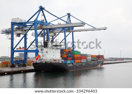 Cargo ship with lot of containers in Copenhagen seaport at misty morning, Denmark - stock photo