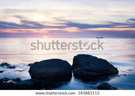 Cargo ships sailing away at the colorful sunset - stock photo