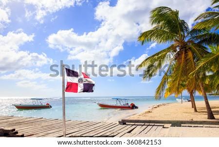 Caribbean beach and Dominican Republic flag on Saona island - stock photo