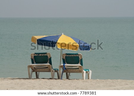 Caribbean beach with two sunloungers under a parasoil - stock photo